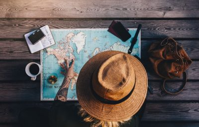 Tourist exploring the world map sitting on wooden floor with compass and other travel accessories. Young woman wearing brown hat looking at the world map.